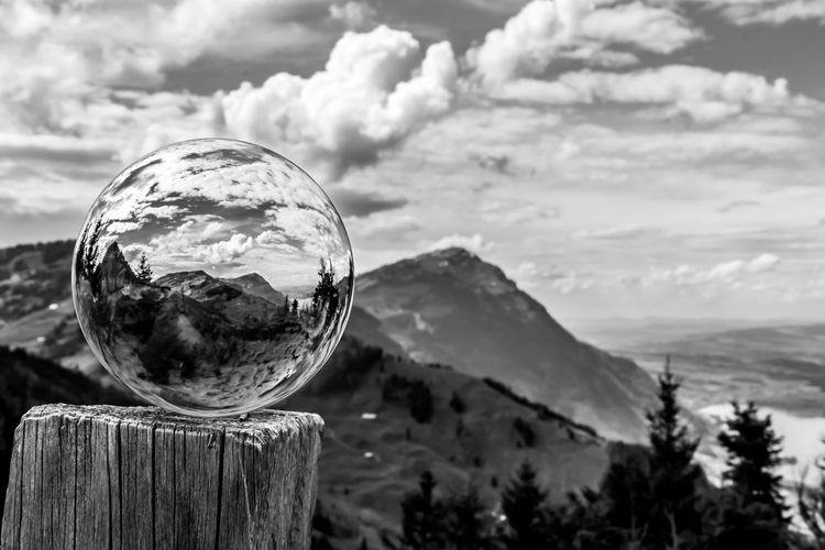 Close-up of crystal ball on landscape against sky