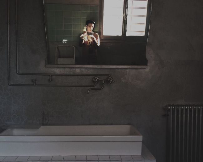 Reflection Of Man Taking Selfie In Mirror At Bathroom