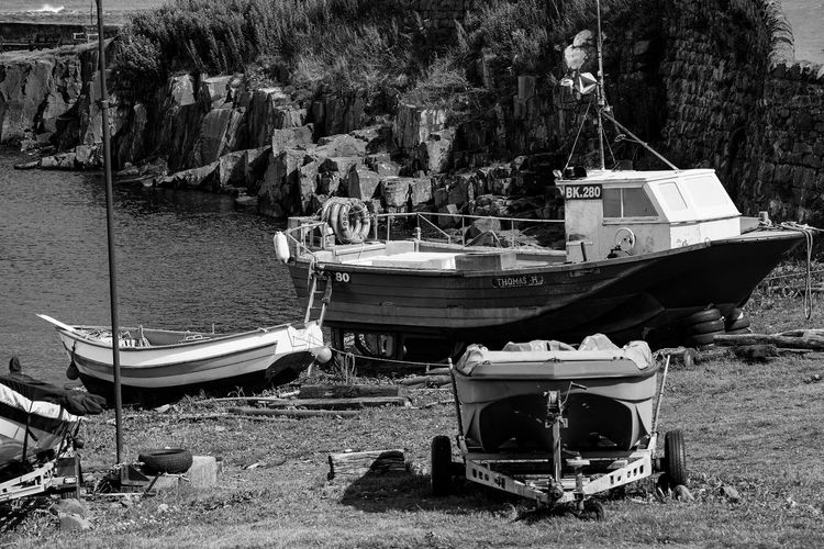 Boats moored on field by river