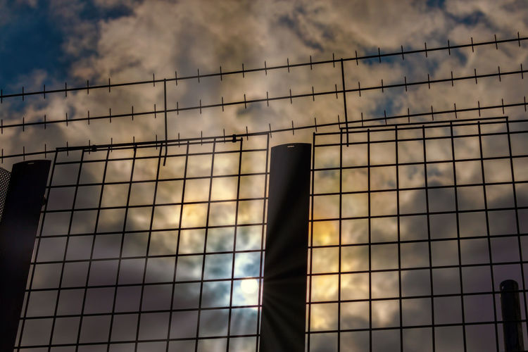 strong fence to separate people Nature Outdoors Day Boundary Barrier Low Angle View Fence Cloud - Sky Sunlight Architecture Sky Division Border Separation Segregation  Prison