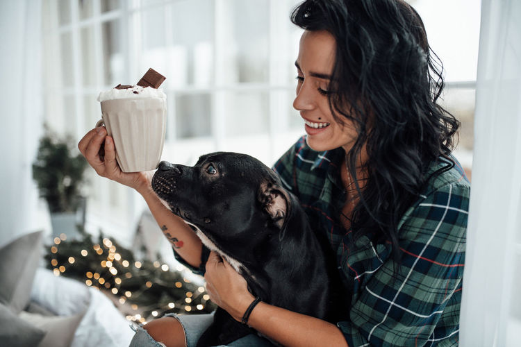 Smiling woman holding hot chocolate while sitting with dog at home
