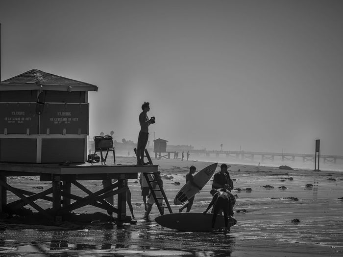 Young male lifeguard watching from lifeguard tower