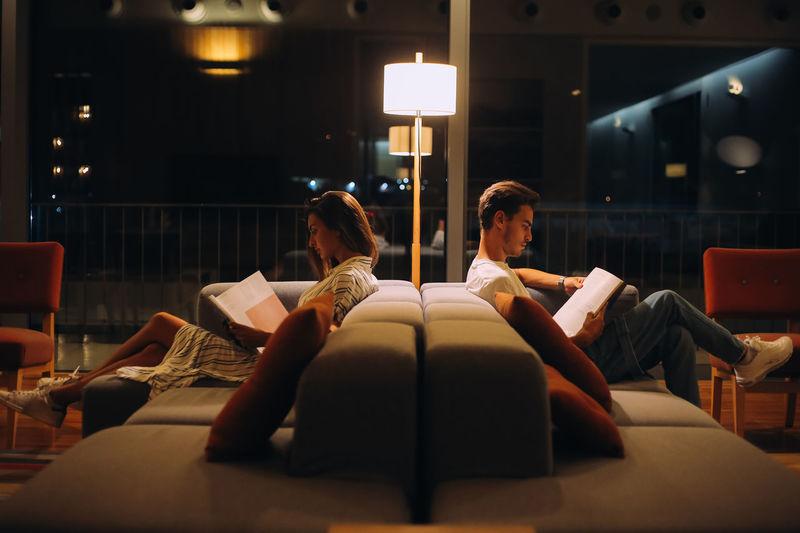 People sitting on sofa in illuminated room