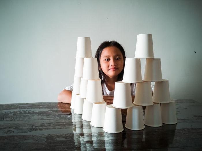 Portrait of smiling girl stacking glasses