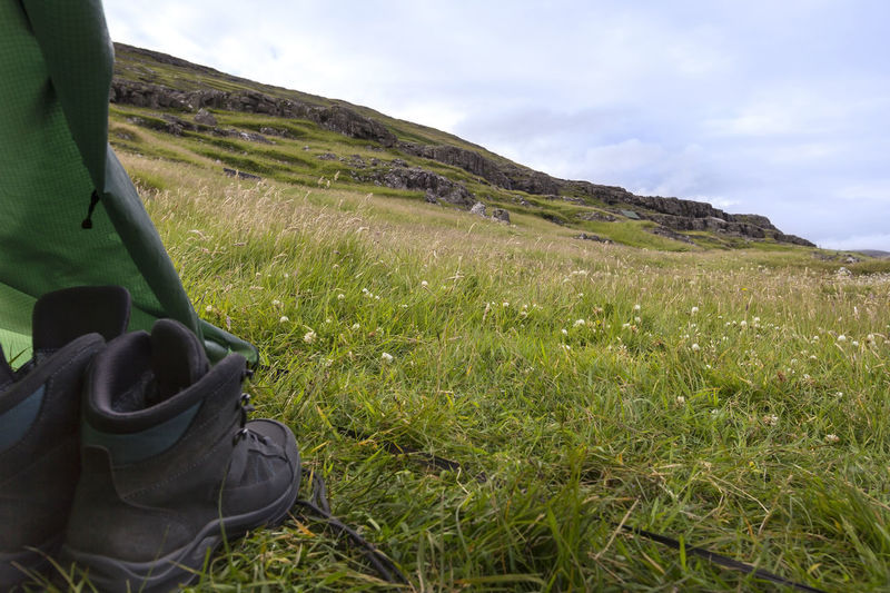 Camping and hiking on the Faroe Islands. Boots Camping Faroer Islands Hiking Adventure Beauty In Nature Cloud - Sky Day Faroe Islands Field Grass Green Color Growth Landscape Meadow Mountain Nature No People Outdoors Scenics Shoe, Hoof, Sabot, Clog, Tub, Tramp Sky Tent Tranquil Scene Tranquility