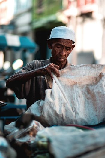 Work hard Elderly Muslim Working Hard Work Old Clothing One Person Real People Adult Hat Men Males  Selective Focus Focus On Foreground Holding Looking Away Lifestyles City Facial Hair