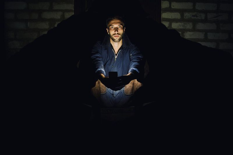 Portrait Of Young Man Using Mobile Phone While Sitting Outdoors At Night