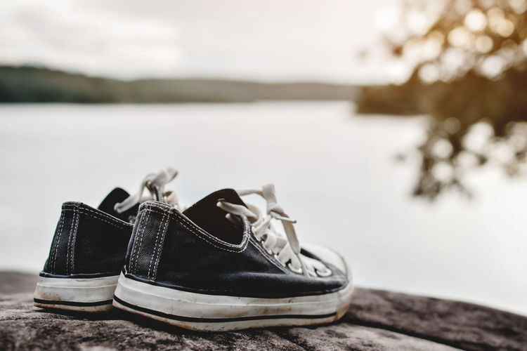 Close-up of canvas shoes on lakeshore