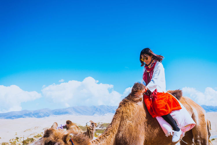 Woman riding camel in desert against sky