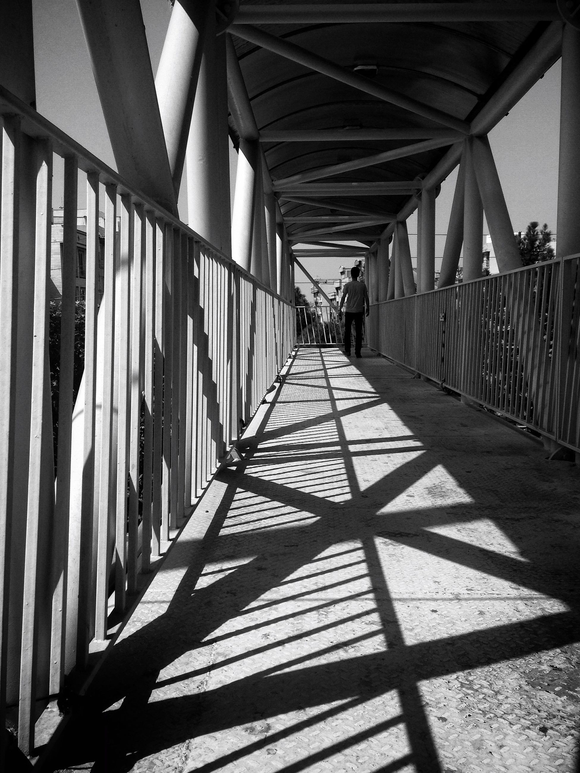 built structure, architecture, the way forward, diminishing perspective, connection, vanishing point, bridge - man made structure, railing, metal, long, transportation, shadow, sunlight, indoors, empty, day, in a row, narrow, footbridge, walkway