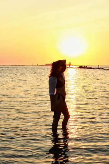 Full length of woman standing on sea against sky during sunset