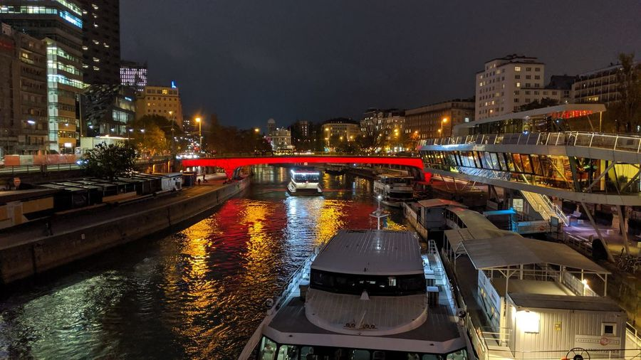 Illuminated bridge over river amidst buildings in city at night