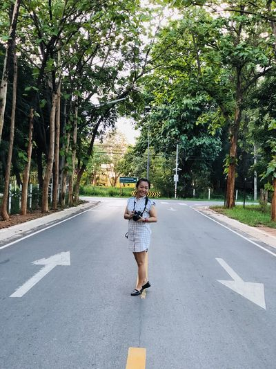 Woman standing on road amidst trees
