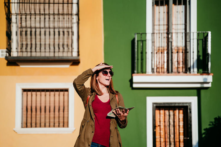 Woman wearing hat standing against building