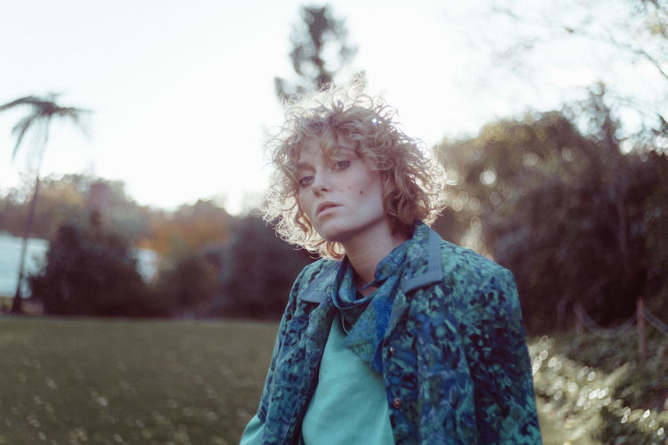 Casual Clothing Curly Hair Day Focus On Foreground Front View Leisure Activity Lifestyles Nature One Person Outdoors Real People Sky Standing The Portraitist - 2017 EyeEm Awards Tree Waist Up Young Adult Young Women