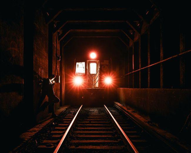 Train in illuminated railroad station at night