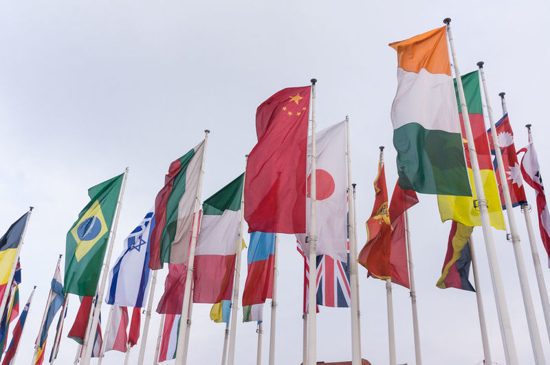 Low angle view of national flags waving against sky