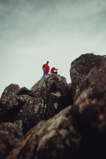 People on rock by mountain against sky