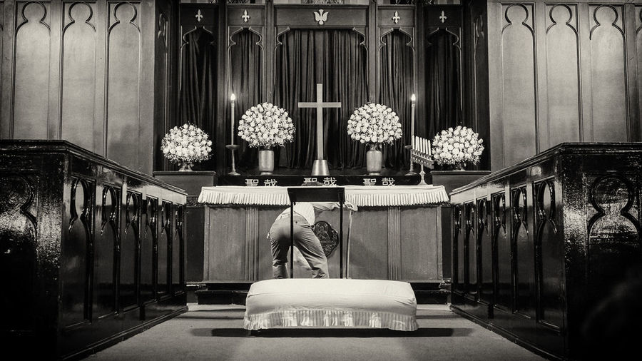 Rear view of man praying to cross while standing at altar