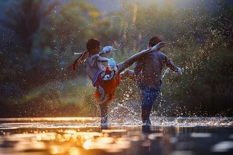 Side view of boys fighting in water