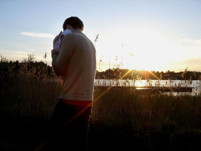 A father carrying his baby daughter in the sunset by a lake. Baby Beauty In Nature Father Lake Lens Flare Nature Outdoors Rear View Sky Sunlight Sunset Water