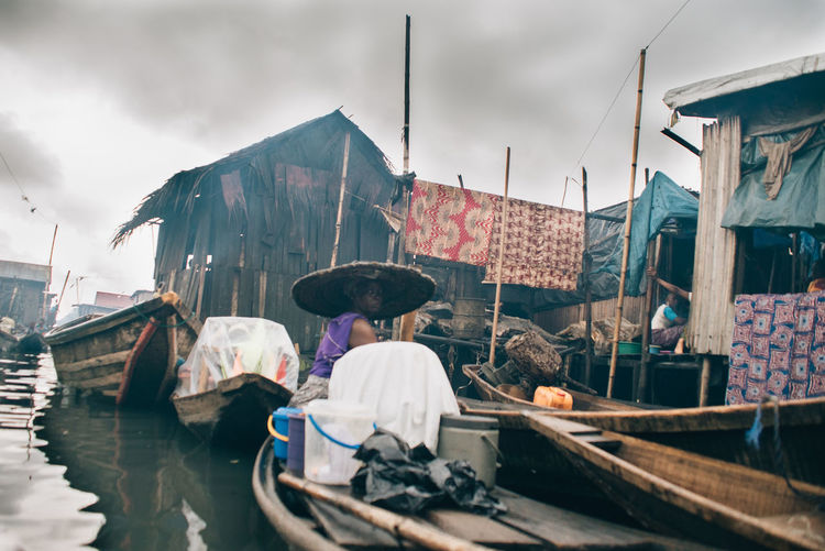 A trader selling on a boat TheWeekOnEyeEM Architecture Building Exterior Built Structure Clothing Cloud - Sky Day Harbor Mode Of Transportation Moored Nature Nautical Vessel Occupation Outdoors People Real People Sailboat Sky Street Transportation Water