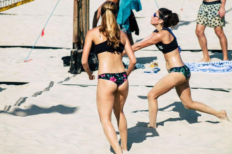 Rear view of friends enjoying at beach