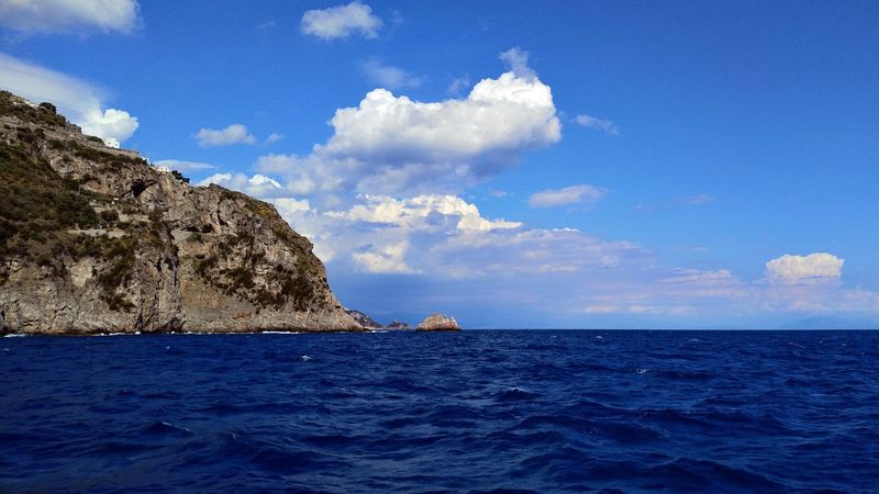 A view of the bay of Positano, where the rocks plunge into the blue. Amalfi Coast Blue Wave Wandering Wanderlust Beauty In Nature Blue Blue Sky Day Horizon Over Water Nature No People Outdoors Positano Scenics Sea Sky Summer Sunset Tourism Tourism Destination Tranquil Scene Tranquility Travel Destinations Water Waterfront