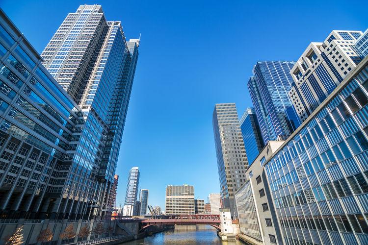 Bridge Over Chicago River Amidst Buildings Against Clear Blue Sky