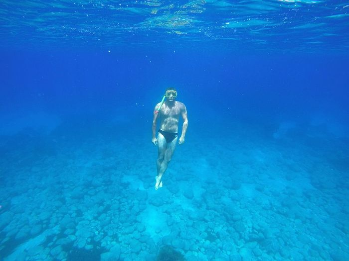 Full length of shirtless man swimming undersea