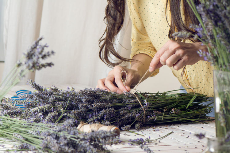 Midsection Of Florist Arranging Bunch Of Lavender Flowers On Table