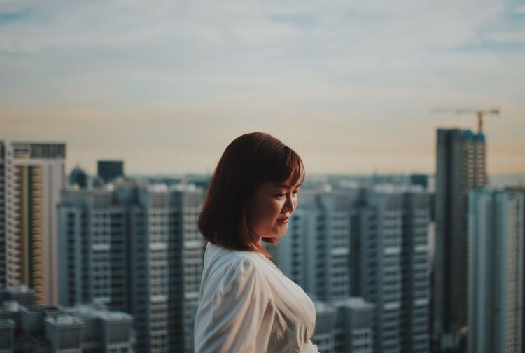 Portrait of woman looking at city buildings against sky