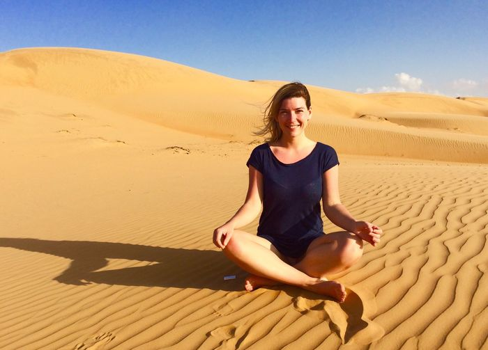 Portrait of smiling young woman sitting on desert against blue sky during sunny day