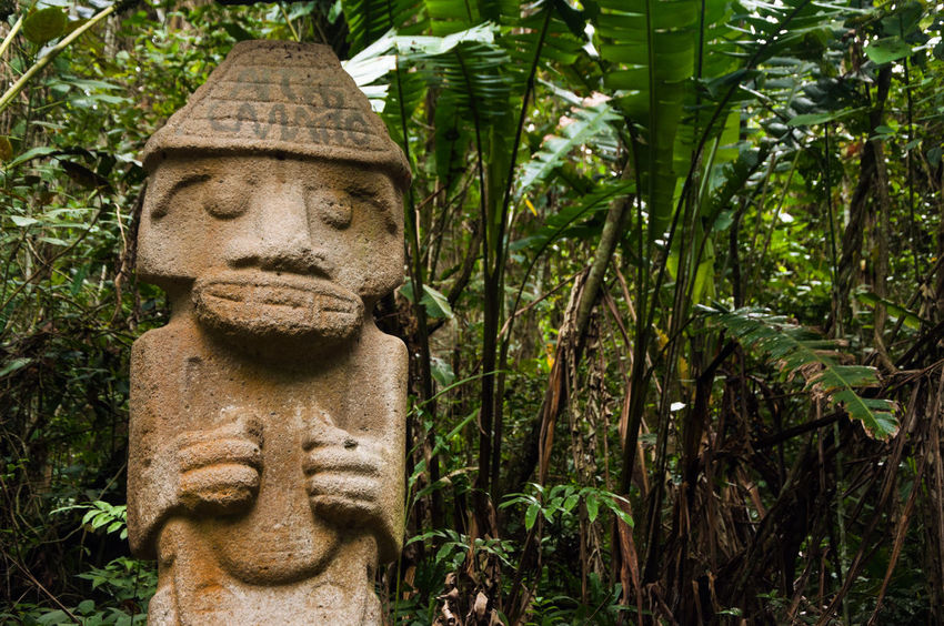An ancient statue that has been vandalized and painted with graffiti. Ancient Art Colombia Columbian  Day Face Famous Grey Historic History Huila  Icon Landmark Monument Old San Agustín Sculpture Statue Stone Symbol Tourism Travel