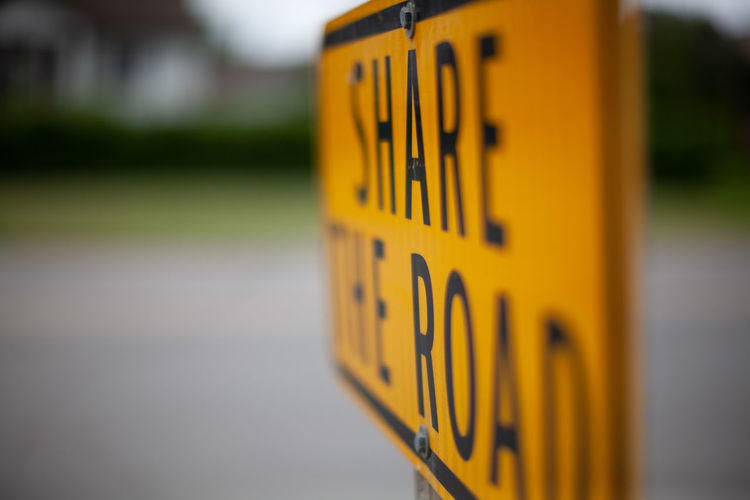 Close-up of yellow sign on road