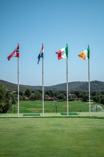 Flags on field against blue sky