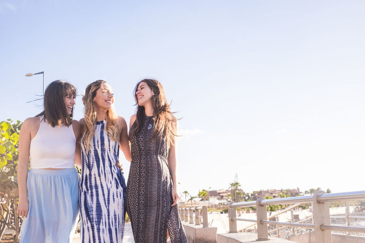 group of three young woman walking in vacation Positive Architecture Beautiful Woman Casual Clothing Chatting Copy Space Day Emotion Fashion Friendship Hair Hairstyle Leisure Activity Lifestyles Long Dress Long Hair Nature Outdoors Sky Standing Sunlight Togetherness Women Young Adult Young Women