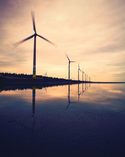 EyeEm Selects Wind Power Wind Turbine Fuel And Power Generation Alternative Energy Environmental Conservation Renewable Energy Sunset Electricity  Reflection No People Technology Windmill Tranquility Water Nature