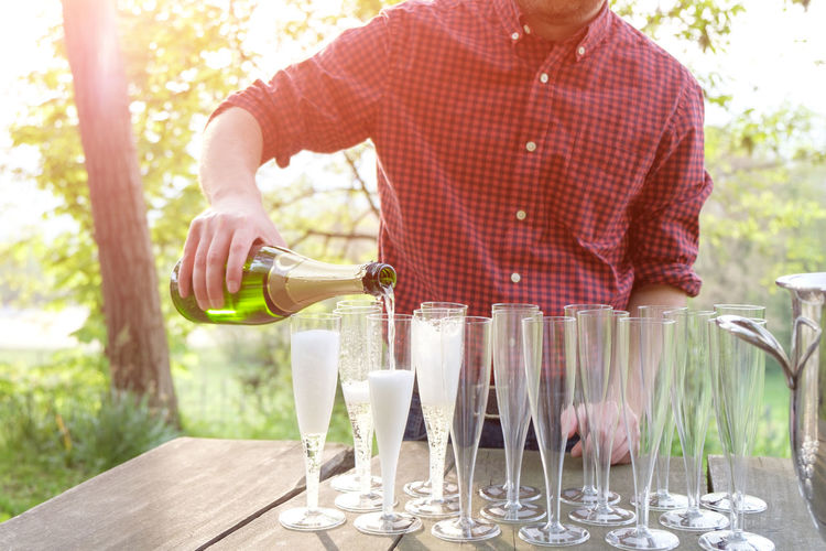 pouring champagne Alcohol Bottle Casual Clothing Day Drink Drinking Glass Food And Drink Glass Holding Household Equipment Men Midsection One Person Pouring Refreshment Standing Table Wine Wineglass