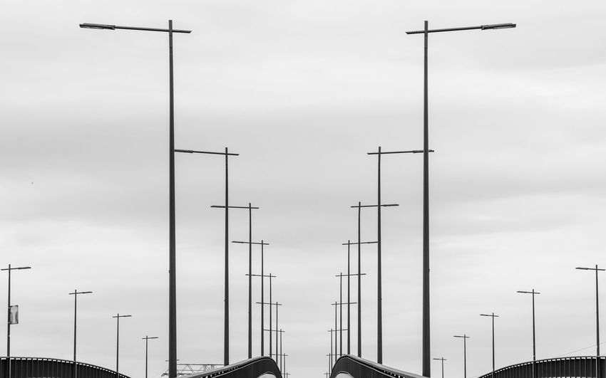 Bridge - Man Made Structure Black And White Urban Minimalism Minimalistic In A Row Sky Low Angle View Cloud - Sky Antenna - Aerial Technology No People Nature Lighting Equipment Street Street Light Day Outdoors Tall - High Connection Architecture Transportation Mode Of Transportation Built Structure