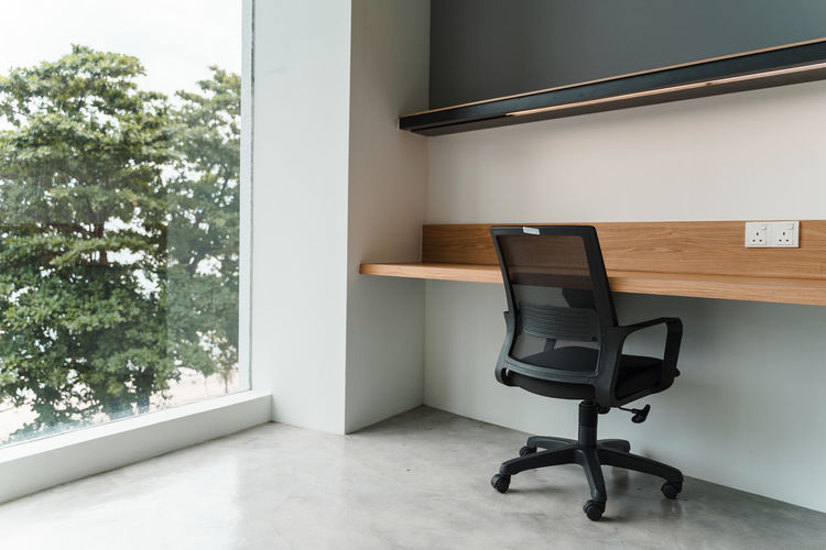 Empty chair by table in office