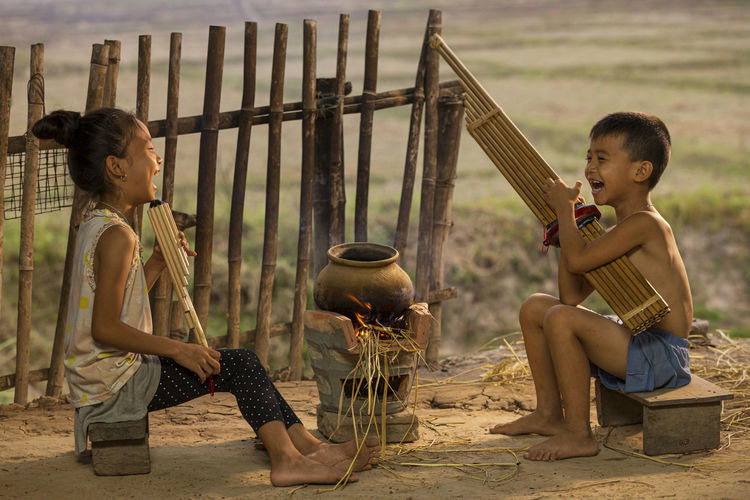 Children playing with umbrella sitting on land
