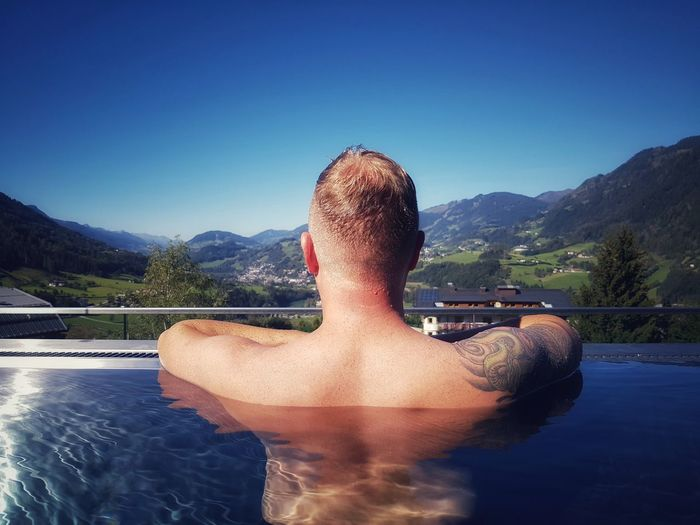 Rear view of shirtless man in infinity pool against sky