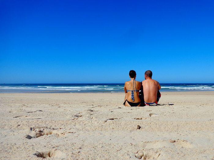 Couple sitting at beach against clear blue sky