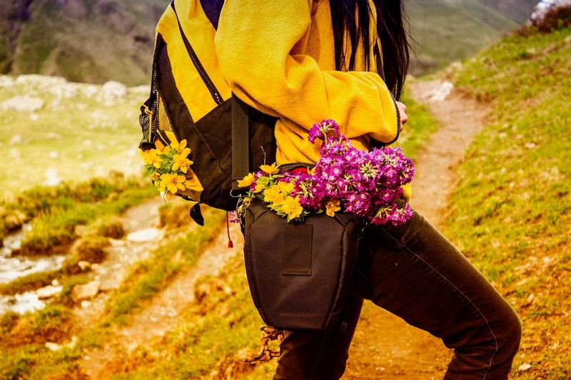 Midsection of woman with flowers in bag walking on mountain