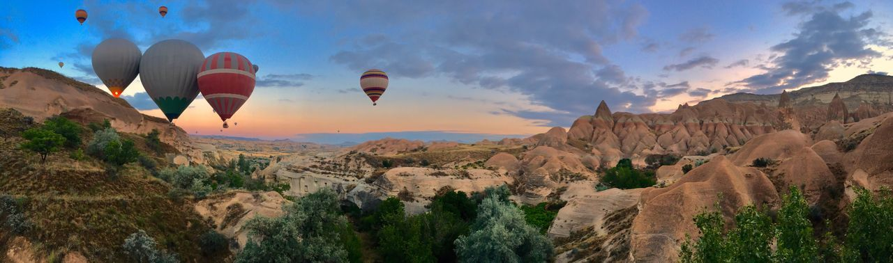 Panoramic shot of hot air balloons in mountains against sky