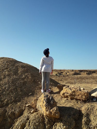 Rear View Of Girl Standing On Rock Against Clear Blue Sky
