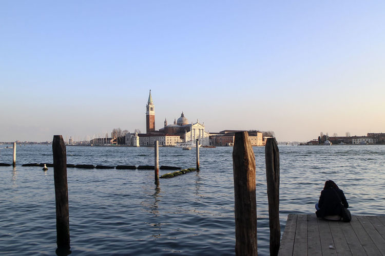 Rear view of woman sitting on jetty by grand canal at san giorgio maggiore church