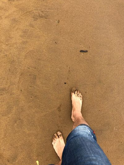Human Body Part Human Leg Body Part Low Section barefoot Personal Perspective Beach Sand One Person Jeans Real People Sunlight Directly Above