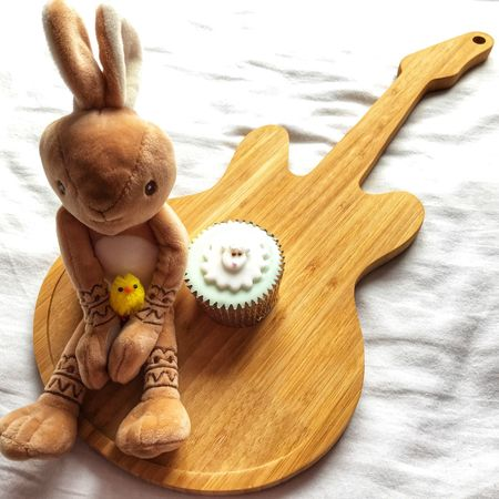 Easter bunny and Easter chick next to an Easter themed iced cupcake on a wooden guitar shaped board with copy space Easter Decoration Easter Ready Guitar Icing Sugar Cupcake Soft Toy Toy Rabbit Easter Chicks Easter Bunny Wood - Material Indoors  Table Easter No People Sweet Food Food Close-up Day